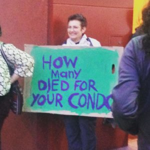 """person holding a sign reading """"how many died for you condo?"""""""