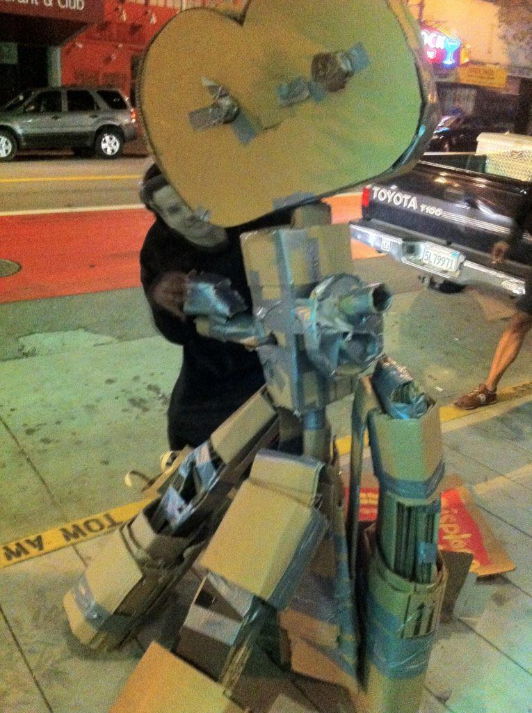 ghost movie director gavin newsom poses behind a cardboard movie camera on a tripod