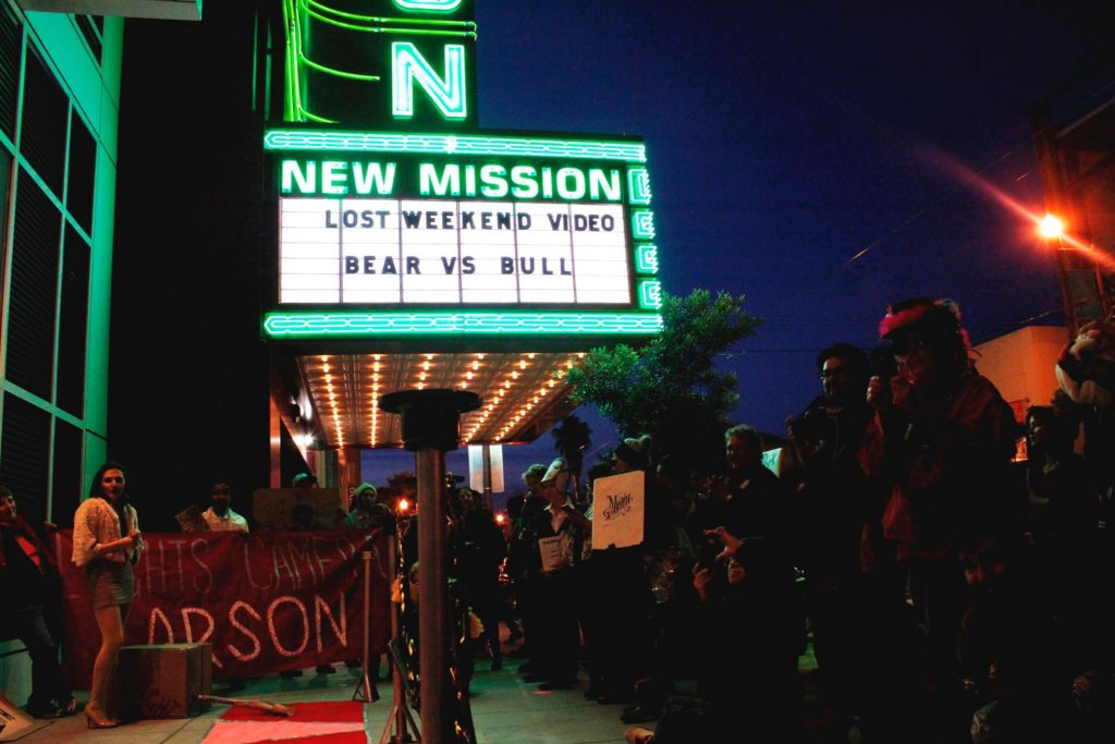 """the marquee new """"new mission"""" marquee looms above the site where people hold a banner that reads """"lights! camera! arson!"""" at the end of a red carpet step-and-repeat in front of the vida condo complex on market between 21st and 22nd"""