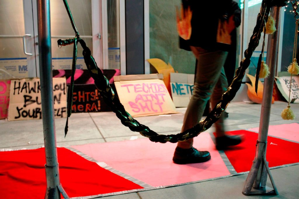 close up a person's feet passing on the red carpet by the stanchion and a row of various protest signs decorating the vacant ground floor retail of the vida luxury condo complex