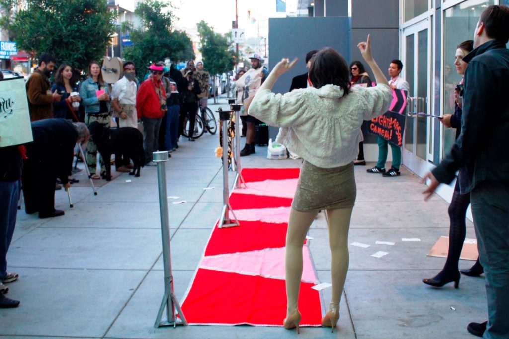 people gather to walk the red carpet step-and-repeat on the mission sidewalk directly in front of the new vida luxury condo complex on mission at 22nd street