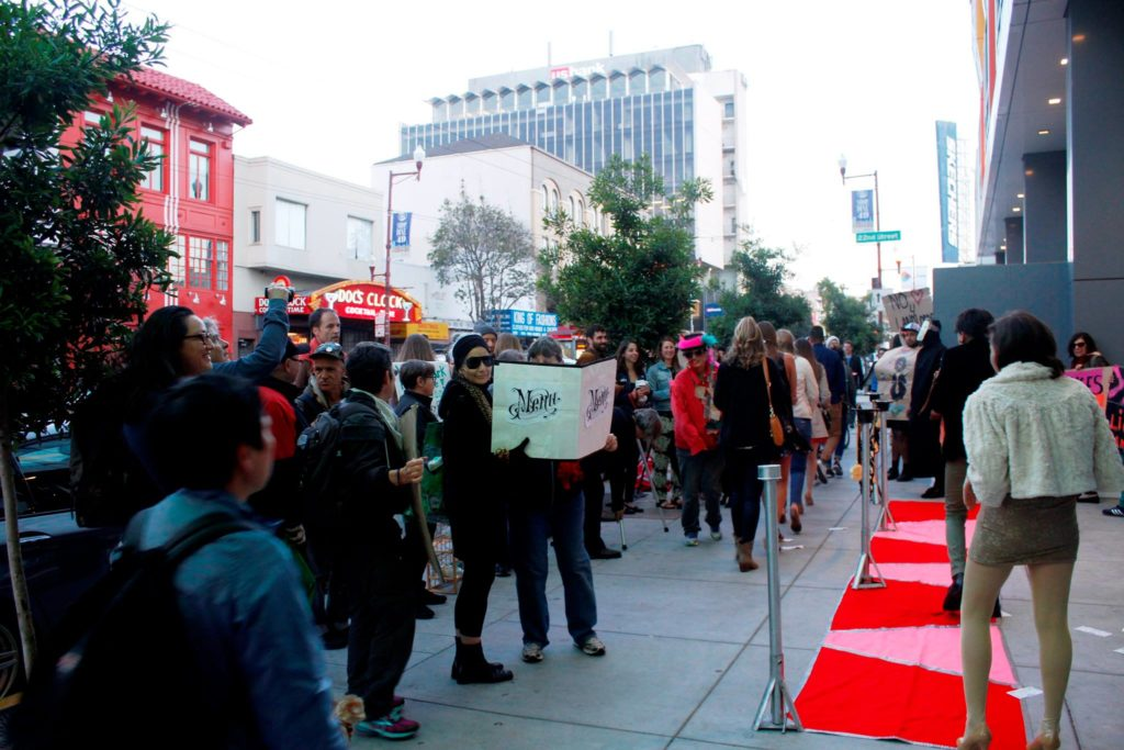 people gather to watch celebrities take to the red carpet step-and-repeat on the sidewalk in front of the vida luxury condo complex at mission and 22nd streets