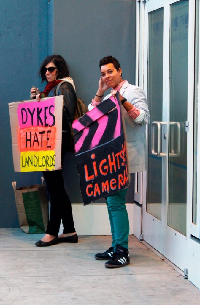 """two people stand holding signs that read """"dykes hate landlords"""" and """"lights! camera! arson!"""""""
