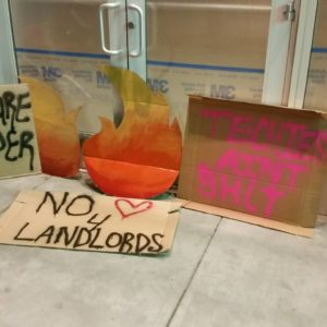 """close-up of signs in front of the vacant ground floor retail of the vida luxury condo complex on mission at 22nd that read """"no <3 for landlords"""" and """"techies ain't shit"""""""