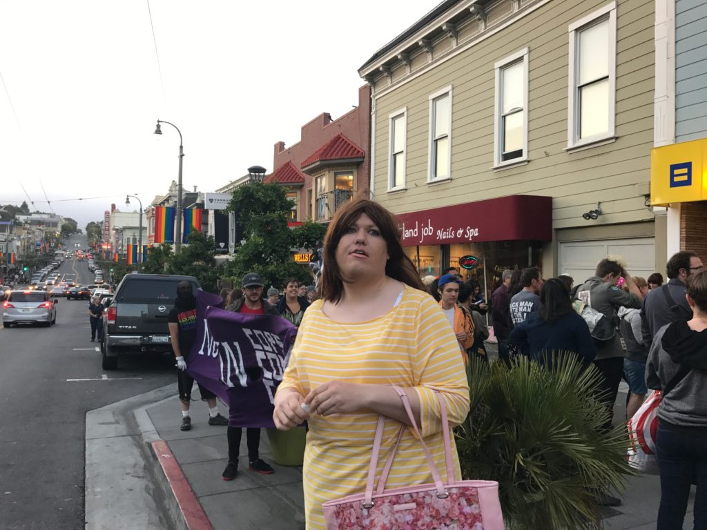 a person joins in on the procession's end at the HRC store at castro near 19th