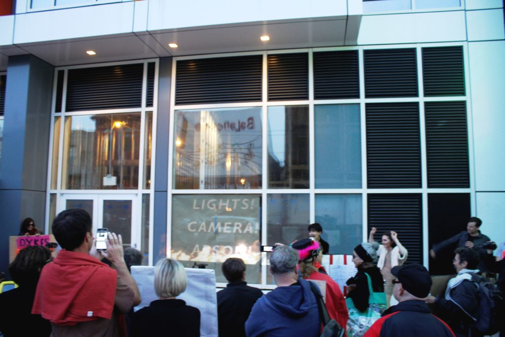 a large crowd gathers on the sidewalk in front of the vacant ground floor retail of the vida luxury condo complex on mission