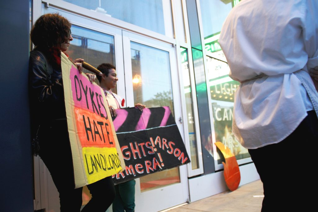 """two people gather in front of the vacant ground floor retail of the vida luxury condo complex holding signs that say """"dykes hate landlords"""" and """"lights! camera! arson!"""""""