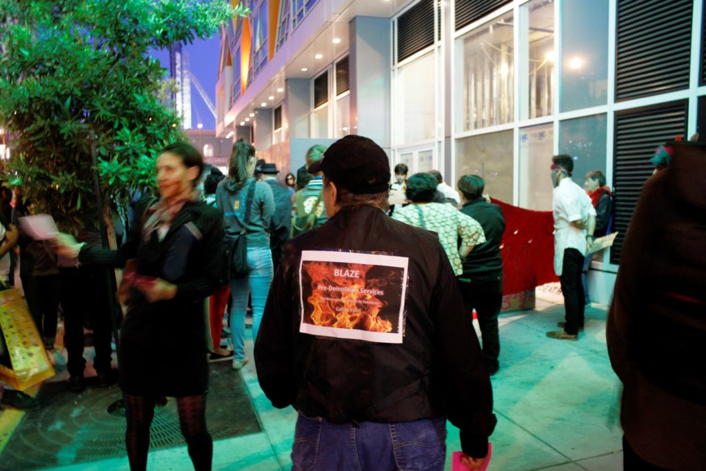 people gathering around the step-and-repeat in front of the vacant ground floor retail of the vida luxury condo complex on mission near 22nd streets
