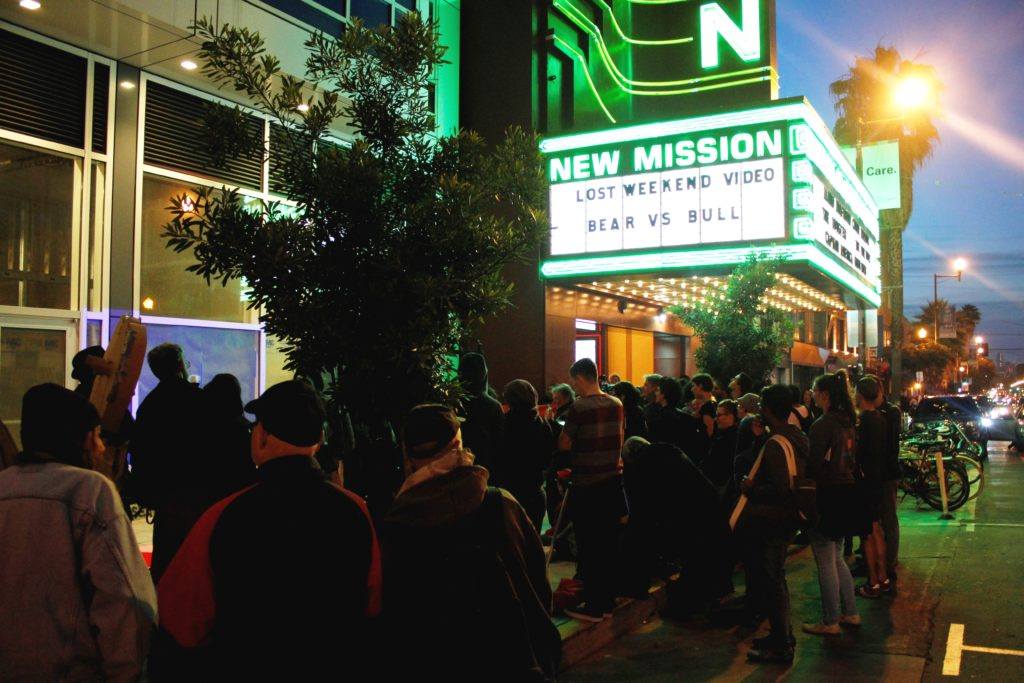 a large crowd of people have gathered on the sidewalk in front of the vacant ground floor retail of the vida luxury condo complex and the new new mission marquee on mission between 22nd and 21st street