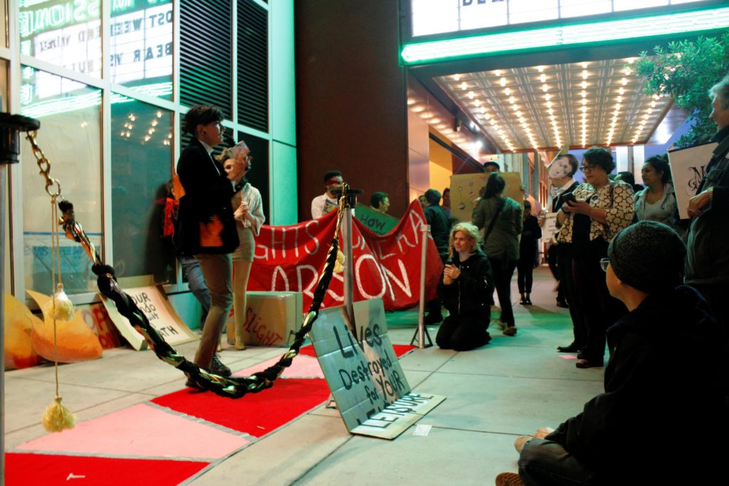 people gathered on the step-and-repeat beneath the marquee of the new new mission in front of the vacant ground floor retail of the vida luxury condo complex on mission between 22nd and 21st street