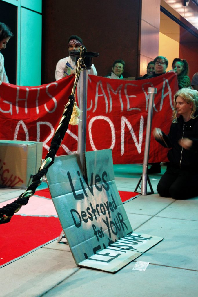 """view of the step-and-repeat where people hold a """"lights! camera! arson!"""" banner and a sign leaning against a stanchion reading """"lives destroyed for your leisure"""""""