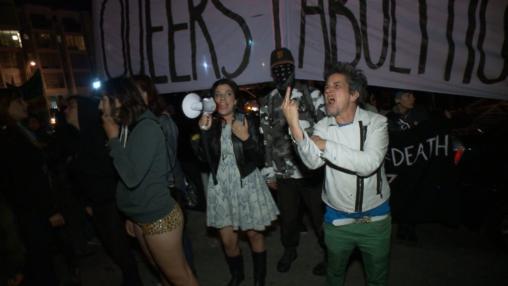 """people protesting the prison themed gay pride rave at kink.com's 14th street and mission entrance with the massive """"pro-sex anti-prison queers for abolition"""" banner in the background"""