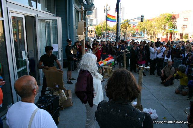 A crowd of people including someone with silvery hair on a bullhorn and 50 or more people who are ready for action.