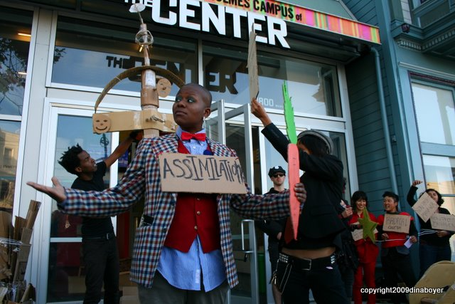 "Image of someone wearing business attire that would befit a dandy living off a sizeable nonprofit salary (the person wears a sign saying ""Assimilation"" and also holds a faux carrot); a cross is being erected in the background and some other action-goers bear signs alongside it in front of the main doors to the LGBT Center in San Francisco."