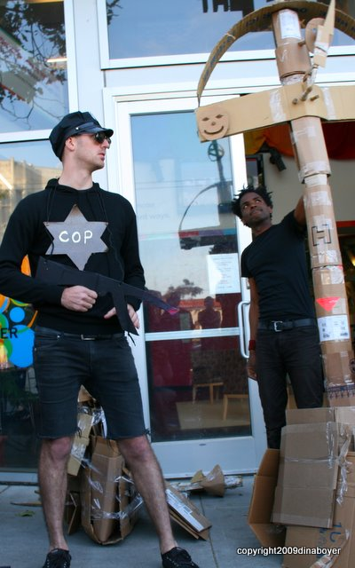 """A dude wearing a giant star that reads """"Cop"""" and carrying an AK-47 stands next to the giant cross erected in front of the LGBT Center in SF."""