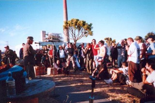 Crowd listens to a speaker with an industrial chimney in the back.