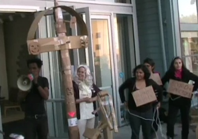 """Another person now has the bullhorn and some people with signs indicating that they were, among other things, that they are part of the system (eg. """"Board of Directors""""), look on."""