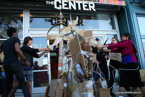 "people gathered around a pile of cardboard props in front of the locked-open main entrance of the lgbt center at 1800 market street, two people cross cardboard swords before competitively striking to break a large cardboard ""stone"" with the cardboard polarity meter in the background"