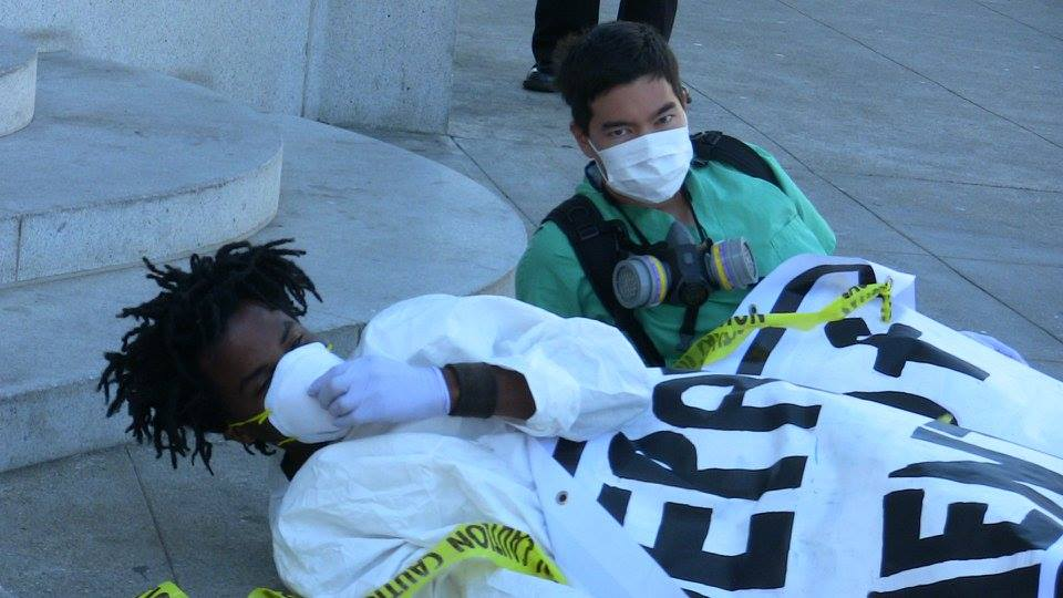 two people laying on the ground apparently ill at the steps of the department of public health under a blanket with respirator face masks and yellow tape