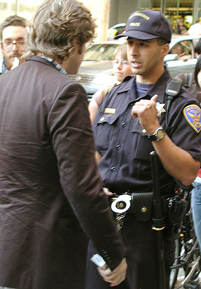 a police officer talking to some person in a suit
