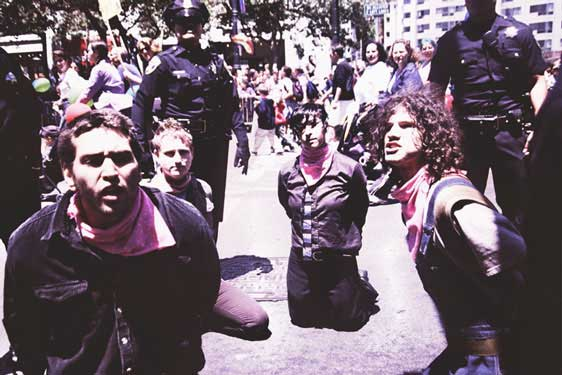 four people handcuffed kneeling surrounded by police in united nations plaza during gay pride
