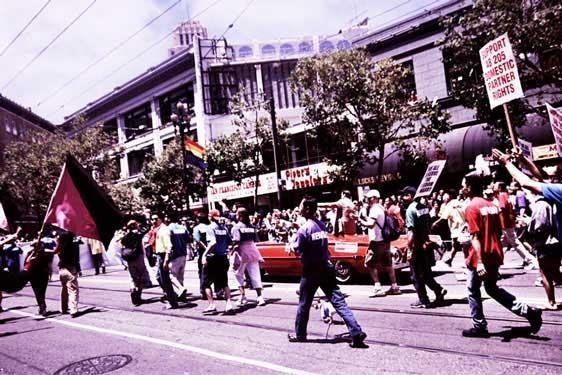 someone holds a black and pink flag alongside newsom's pride motorcade on market street