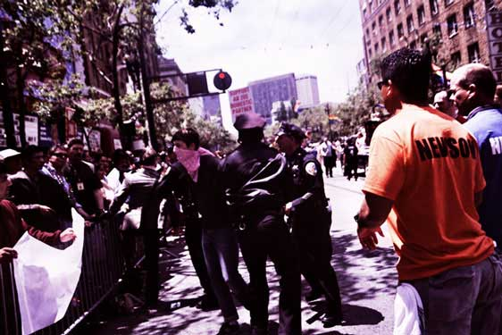 police strongarm a person in a pink bandana out of the market street pride parade route