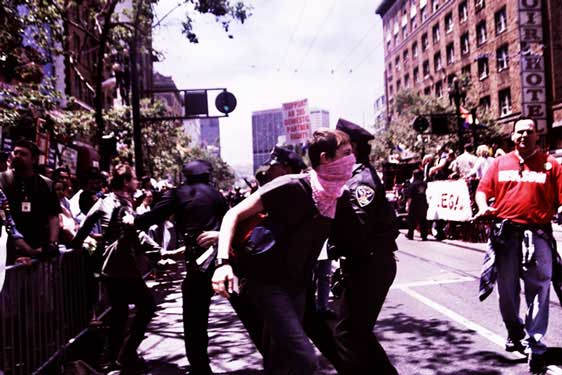 police forcefully apprehending person in pink bandana covering face
