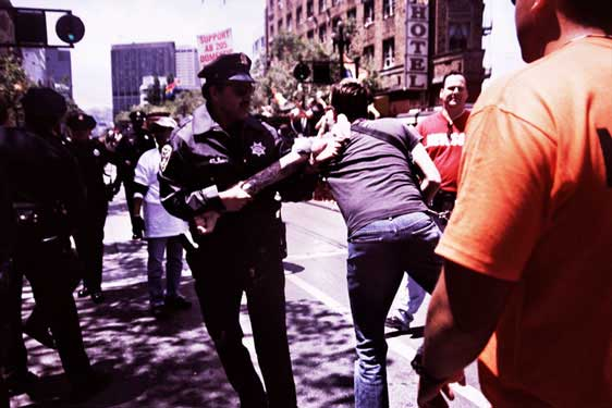 police and newsom parade volunteer removing person from parade route