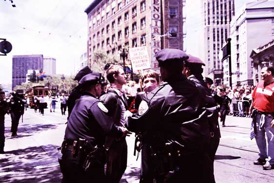 police detaining people in pink bandanas in the pride parade route on market street