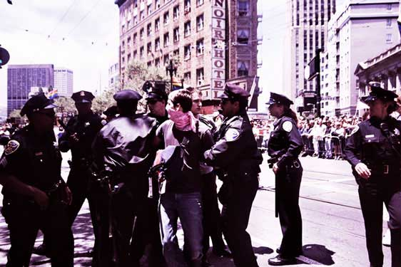 person in pink bandana being mobbed by a large group of police inside the market street gay pride parade route