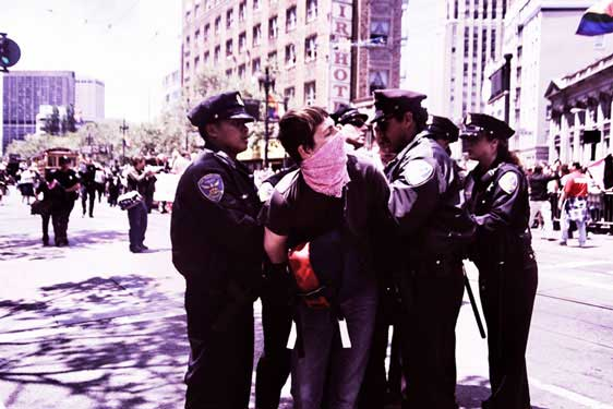 police handcuffing person in pink bandana in the market street pride parade route