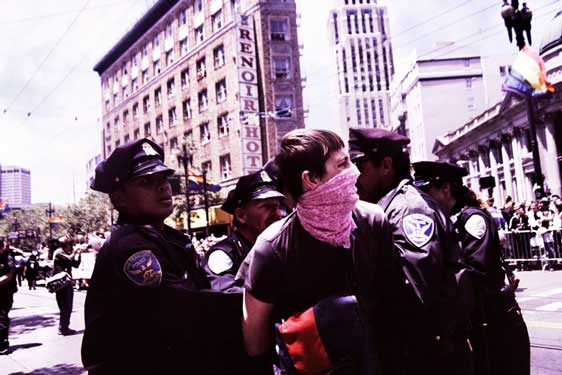 medium shot of police cuffing and strong-arming person in pink bandana in the market street pride parade route