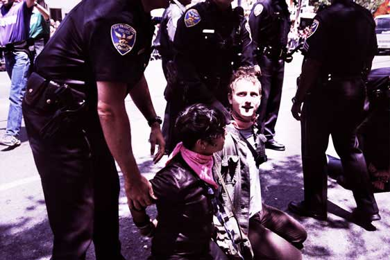 police officers loom over two handcuffed people kneeling in pink bandanas