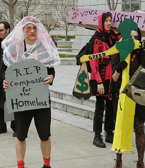 "people dressed as bloodstained mourners with blood and lace, one holding a coffin labeled ""the voice of dissent"", another with a cardboard tombstone reading ""r.i.p. compassion for the homeless"""
