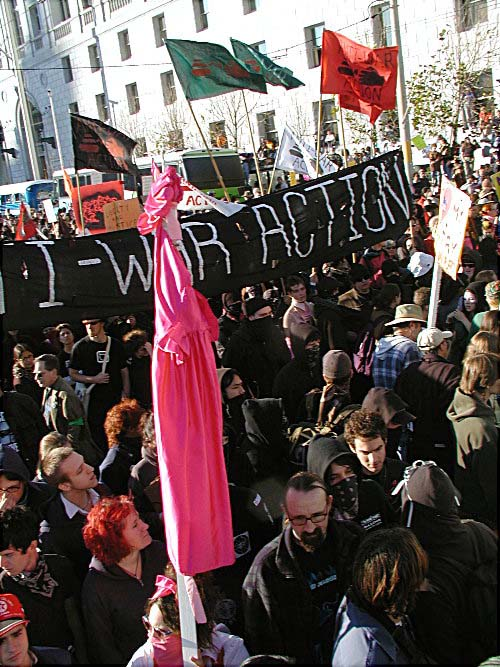 "overhead shot of tons of people marching in front of the black ""anti-war action"" banner"