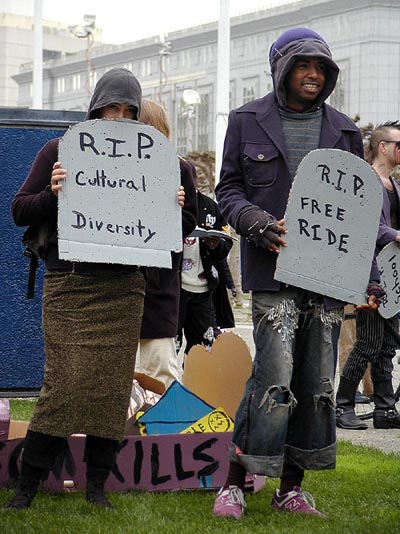"two mourners carrying cardboard tombstones reading ""r.i.p. cultural diversity"" and ""r.i.p. free ride"" respectively"