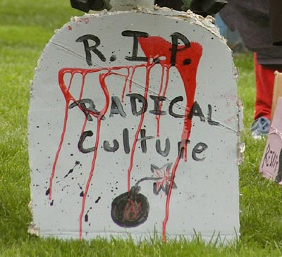 "fake blood stains a cardboard tombstone reading: ""r.i.p. radical culture"""