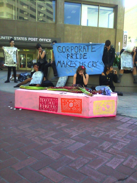 "people gathered at the planter in the area in front of the post office at market and hayes with a pink cardboard coffin plastered with multicolored queer papel picada and wilted violet hyacinth and magenta gladioli on the lid holding a blue ""corporate pride makes us cry"" banner"