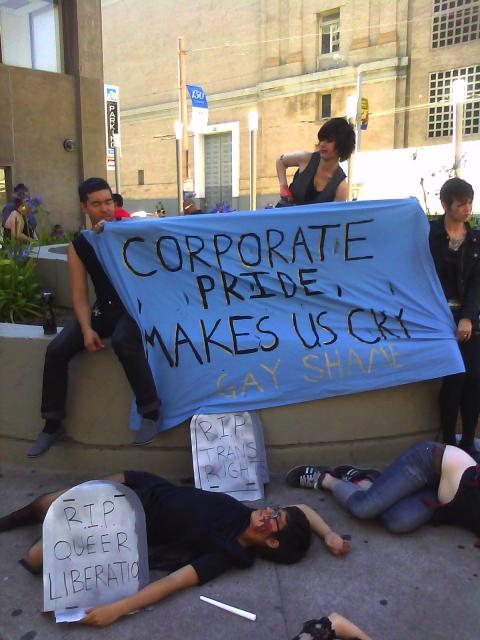 "people holding a blue banner that reads ""corporate pride makes us sick"" sitting on the planter in front of the post office at market and hayes and some other people apparently playing dead on the ground with cardboard tombstones reading ""r.i.p. queer liberation"" and ""r.i.p. trans rights"""