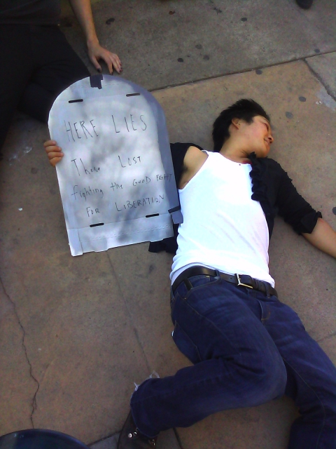"a person apparently playing dead on the ground holding a cardboard tombstone reading ""here lies those lost fighting the good fight for liberation"""