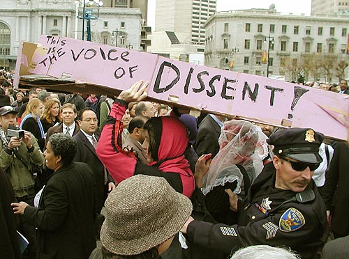 "people carrying a pink coffin that reads ""this is the voice of dissent"" through a crowd at newsom's inauguration ceremony at civic center plaza"
