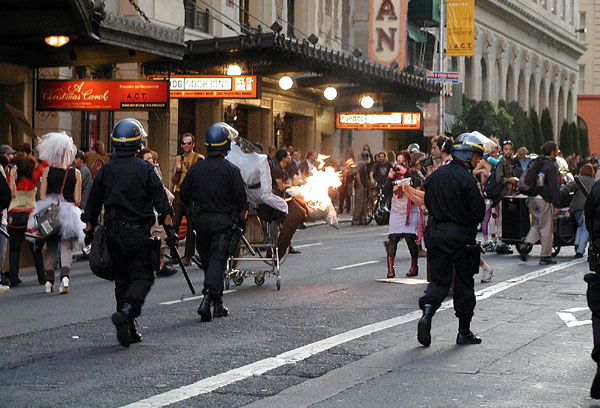 riot police advancing from mason up geary toward a shopping cart on fire and a group of people who have taken the street in front of the curran theatre
