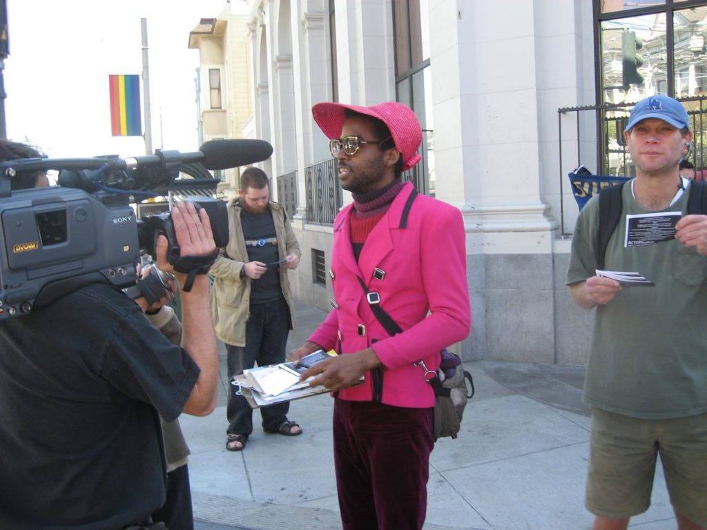a person is being interviewed by television media at the meet up place for the caravan on castro at 18th