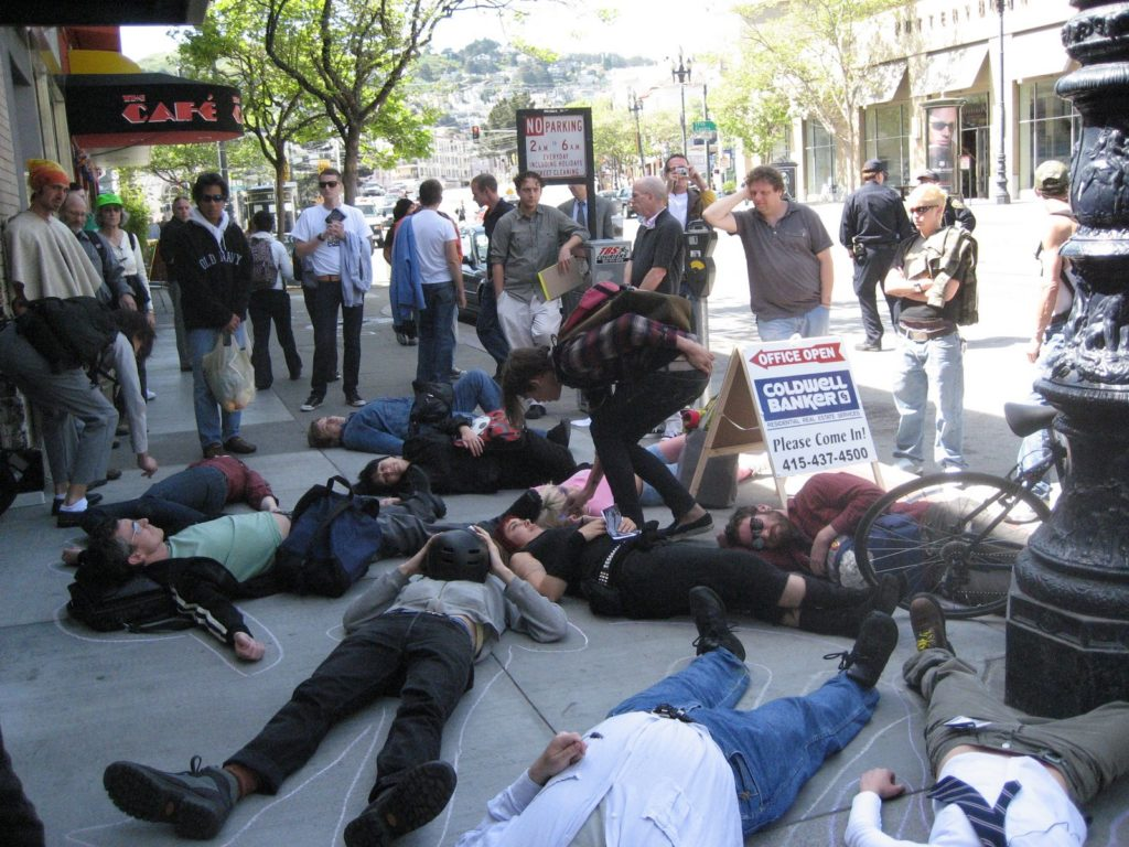 a large group of people stage a die-in on market street on the sidewalk in front of the new coldwell banker location