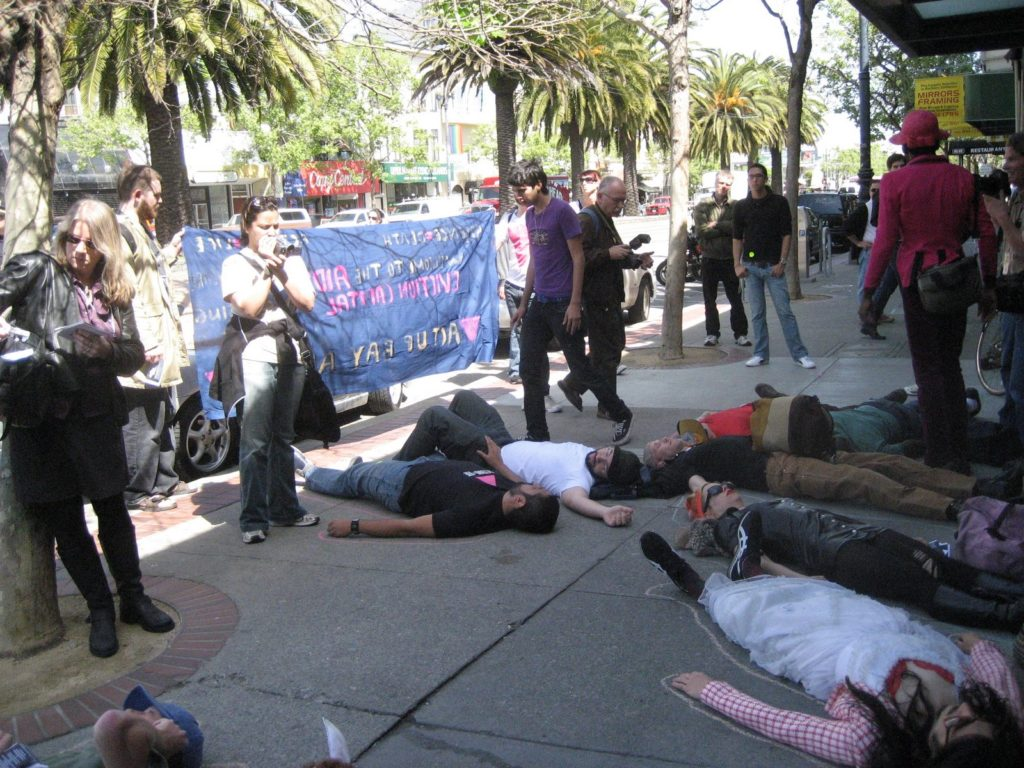a larger group of people staging a die-in on market street near castro in front of the new coldwell banker location