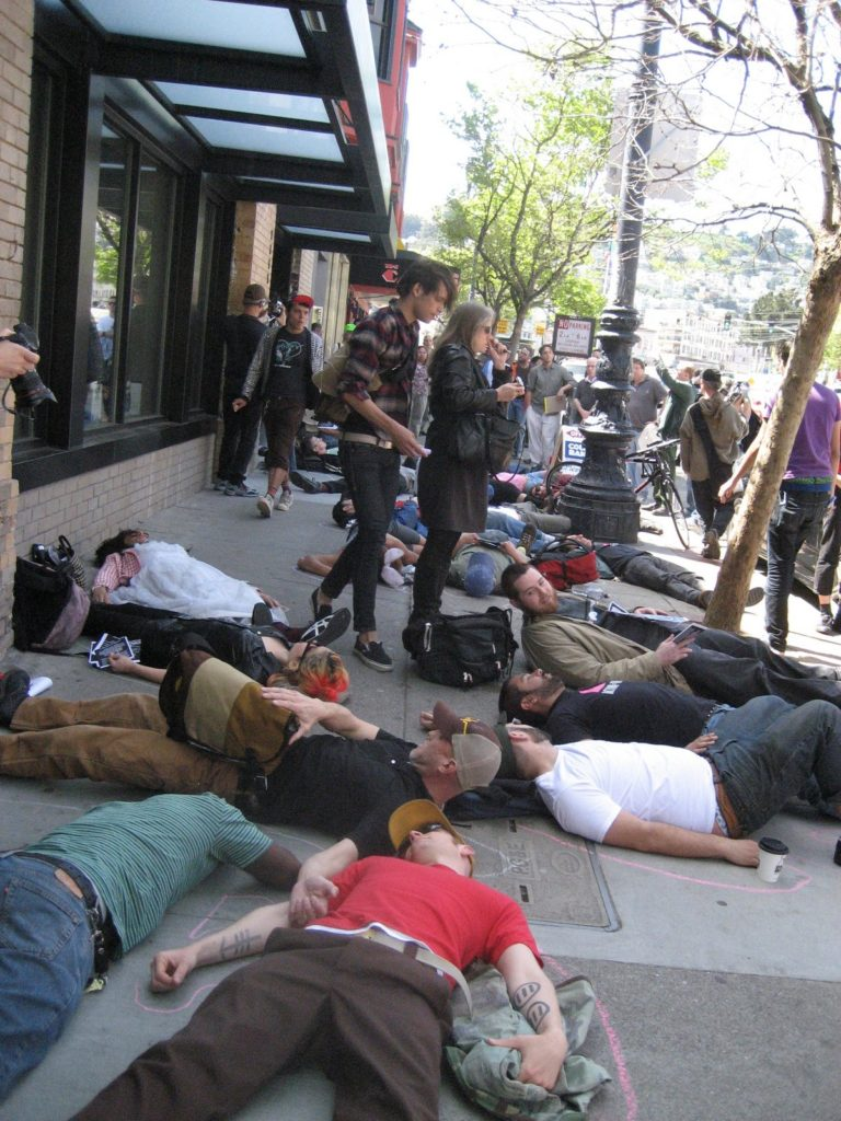 a large people staging a die-in on the sidewalk in front of the new market street coldwell banker location near castro