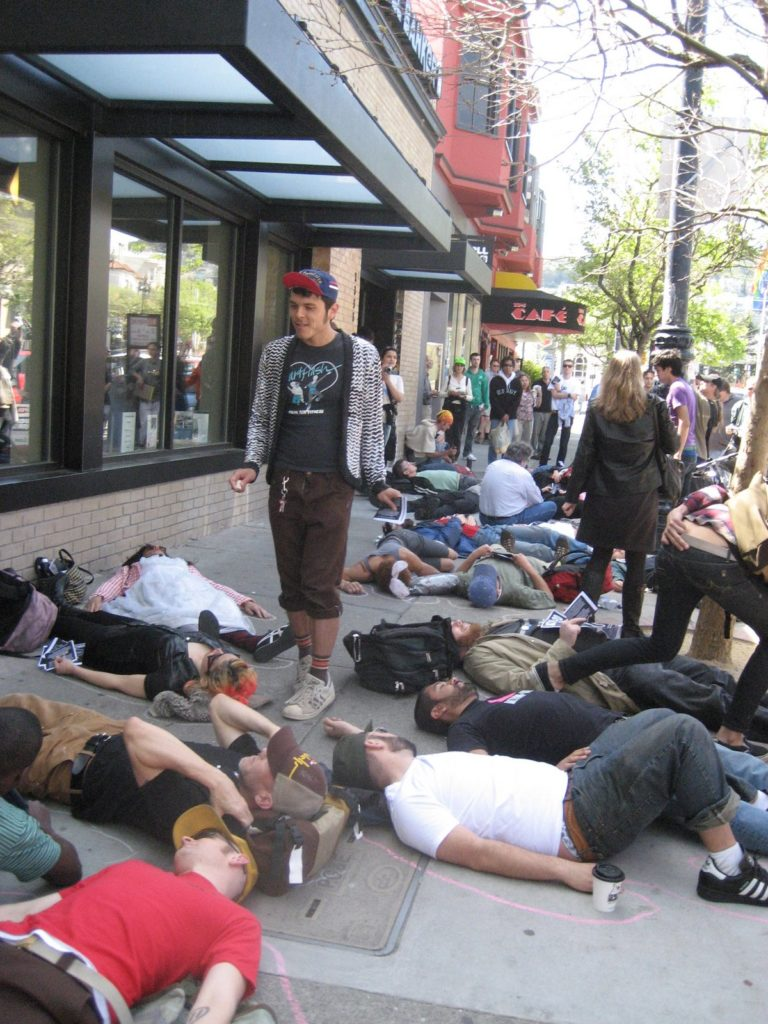 a large people are staging a die-in on the sidewalk in front of the coldwell banker location on market near castro