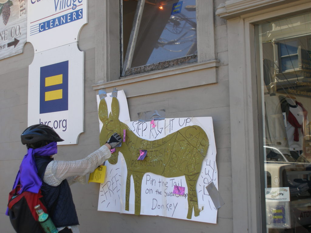 person playing pin the tail on the sweatshop donkey on the side of the hrc.org store exterior at castro on 19th