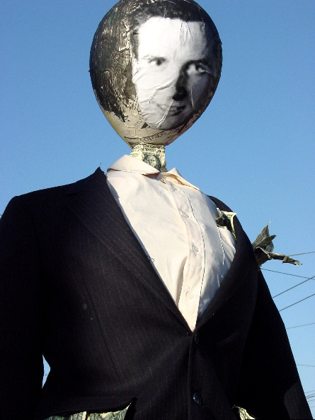 close-up of a gavin newsom effigy with a b/w photocopied image of his face plastered on a balloon in a pinstriped suit stuffed with money